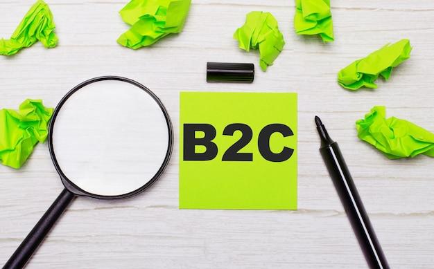 Слово b2c бизнес для потребителя написано на зеленой записке рядом с увеличительным стеклом и черным маркером на деревянном столе