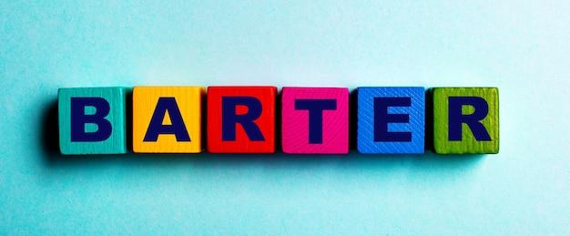 Слово barter написано на разноцветных ярких деревянных кубиках на голубой поверхности.