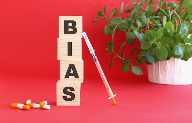 Bias라는 단어는 의료용 약물로 붉은 색 표면에 나무 큐브로 만들어져 있습니다.
