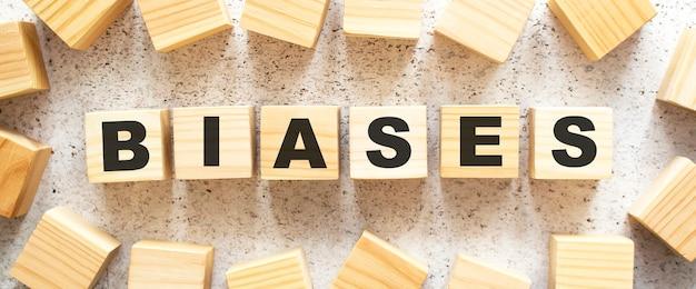 バイアスという言葉は、明るい背景に上面図の文字が付いた木製の立方体で構成されています。作業スペース。
