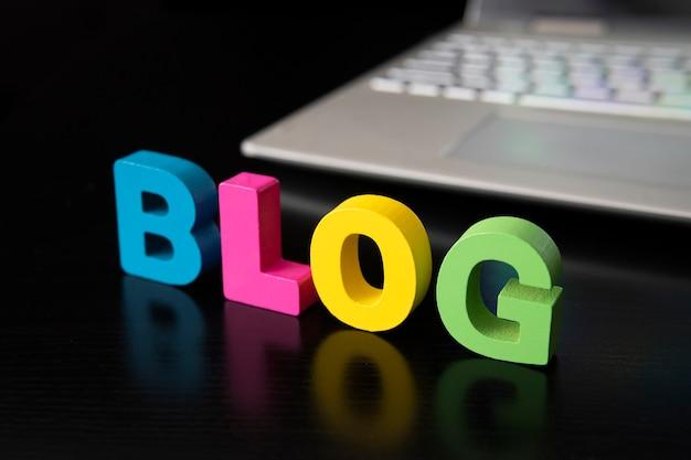 Слово блог на черном столе против серого ноутбука. концепция развития видеоблогинга в мире.