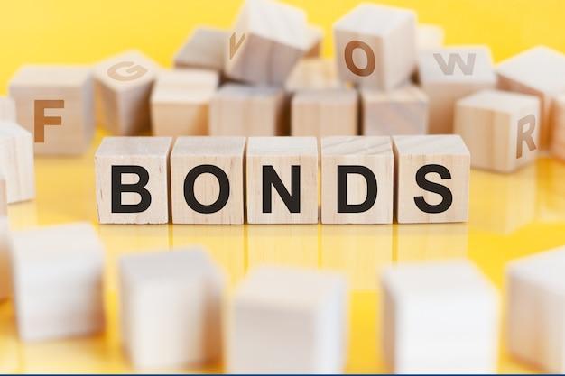 Слово «облигации» написано на деревянной конструкции из кубиков. блоки на ярком фоне. финансовая концепция. выборочный фокус