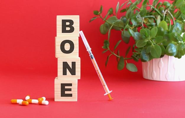Слово bone состоит из деревянных кубиков на красном фоне с медицинскими препаратами.
