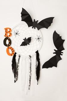 Слово «бу», летучие мыши и ловец снов с пауками на белом фоне - это концепция хэллоуина.