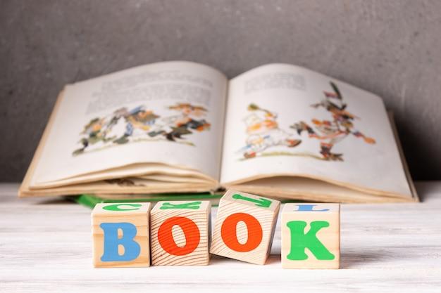 책이라는 단어는 어린이 책의 배경에 큐브가 쌓여 있습니다.