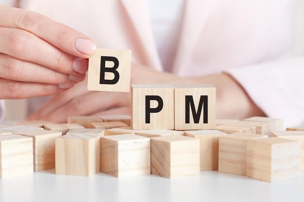 女性の手、ピンクの背景を持つ木のおもちゃのブロックの単語bpm。ビジネスコンセプト。 bpmはビジネスプロセス管理の略です