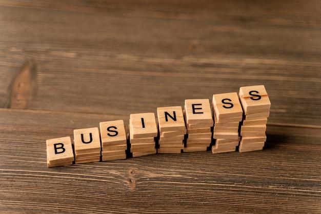 「ビジネス」という言葉は、はしごの形をした木製のブロックが並んでいます