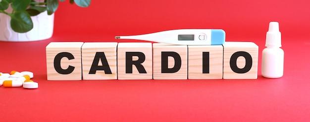 Cardio라는 단어는 의료용 약물과 함께 빨간색 표면에 나무 큐브로 만들어져 있습니다.
