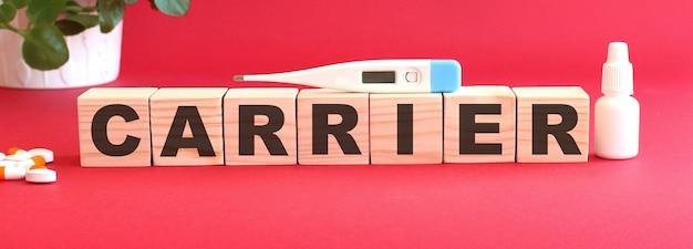 단어 carrier는 빨간색 배경에 나무 큐브로 구성됩니다.