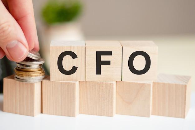 나무 큐브에 쓰여진 단어 cfo. 사람의 손이 입방체 표면에 동전을 놓습니다. 비즈니스 및 금융 개념. cfo (최고 재무 책임자)의 약자