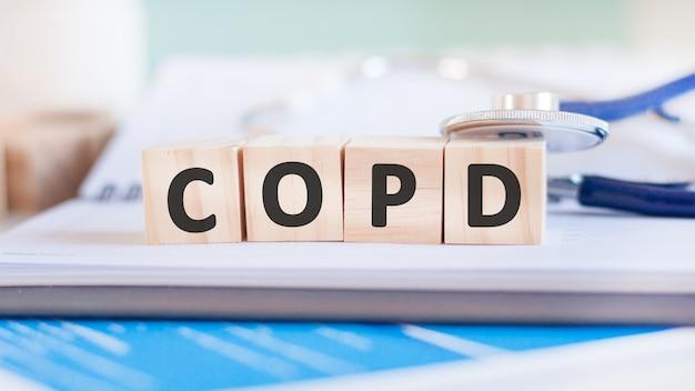 Copdという言葉は、紙の表面の聴診器の近くにある木製の立方体に書かれています