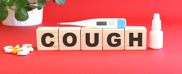 咳という言葉は、赤い背景に医薬品が入った木製の立方体でできています。医療の概念。