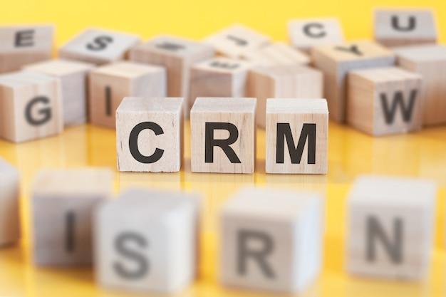 Crm이라는 단어는 나무 큐브 구조에 작성됩니다. 밝은 배경에 블록입니다. 금융 개념입니다. 선택적 초점. crm - 고객 관계 관리를 위한 총기
