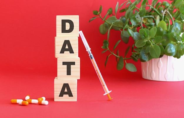 データという言葉は、赤い背景の上の木製の立方体で作られています
