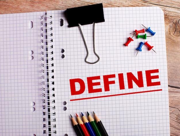 Слово define написано в блокноте возле разноцветных карандашей и кнопок на деревянной поверхности.