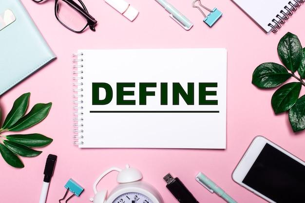 Слово define написано в белой записной книжке на розовом фоне в окружении деловых аксессуаров и зеленых листьев.