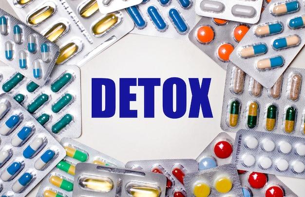Слово детокс написано на светлом фоне в окружении разноцветных упаковок с таблетками. медицинская концепция
