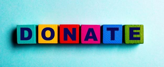 寄付という言葉は、水色の表面の色とりどりの明るい木製の立方体に書かれています