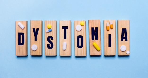 Dystoniaという言葉は、丸薬の近くの水色のテーブルの上の木製のブロックに書かれています。