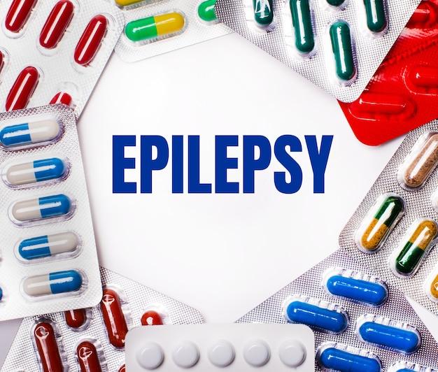 Слово эпилепсия написано на светлой поверхности в окружении разноцветных упаковок с таблетками.