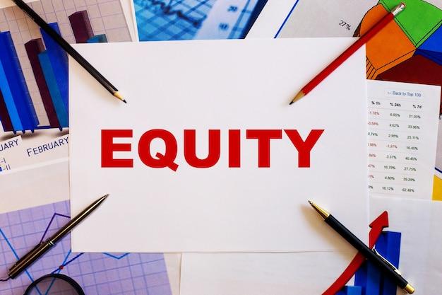 Слово equity написано красным на белом фоне рядом с графиками, ручками и карандашами. бизнес-концепция