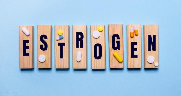 Слово эстроген написано на деревянных блоках на голубом столе возле таблеток. медицинская концепция
