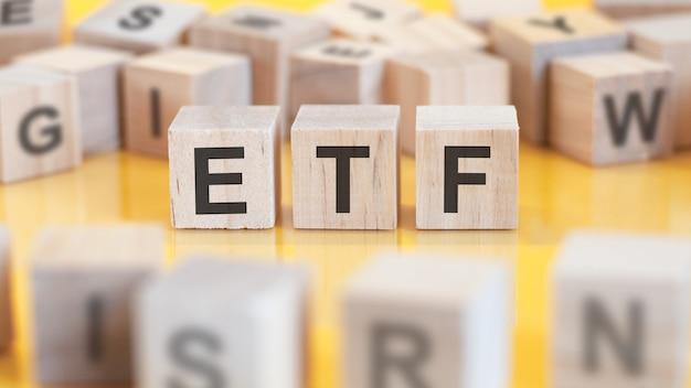 Слово etf написано на деревянной конструкции из кубиков. блоки на ярком фоне. финансовая концепция. выборочный фокус. etf - выстрел для биржевого фонда