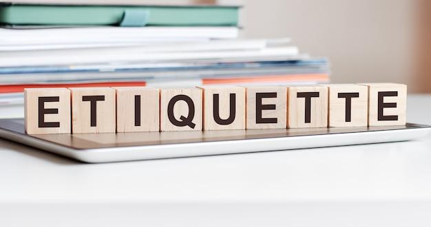 エチケットという言葉は、メモ帳の上に立っている木製の立方体に書かれており、背景にはドキュメントのスタック、選択的な焦点があります。ビジネス、教育、財務の概念に使用できます