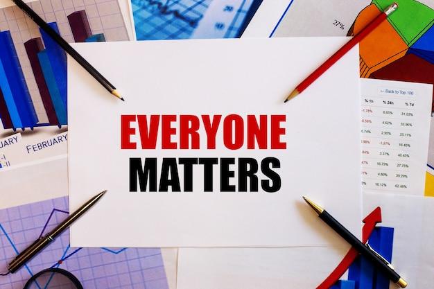 Everyone matters라는 단어는 컬러 그래프, 펜 및 연필 근처의 흰색 표면에 작성됩니다.