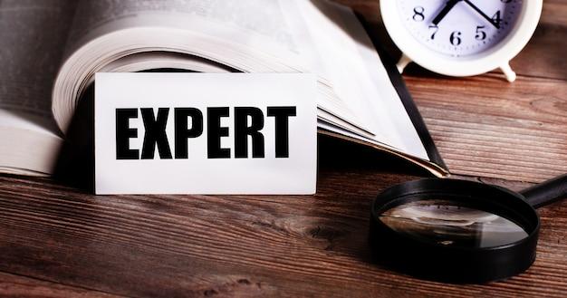 Слово эксперт написано на белой карточке рядом с открытой книгой, будильником и увеличительным стеклом