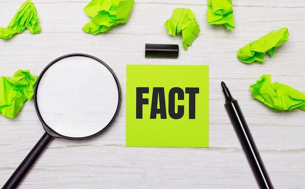 虫眼鏡の横にある緑色の付箋紙と木製のテーブルの黒いマーカーに書かれたfactという単語