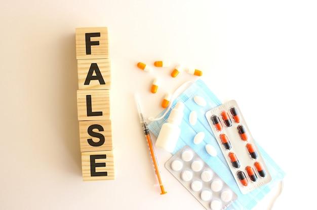 False라는 단어는 흰색 배경에 나무 큐브로 만들어졌습니다. 의료 개념입니다.