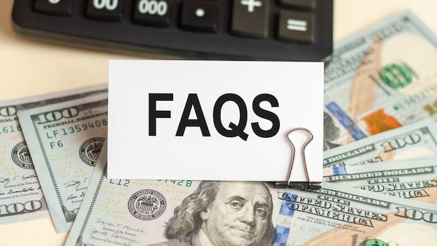 흰색 카드에는 faqs라는 단어가 적혀 있습니다. 100 달러 지폐와 계산기의 배경에 카드. 비즈니스 개념