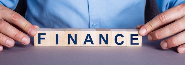 Слово финансы составлено мужчиной из деревянных кубиков.