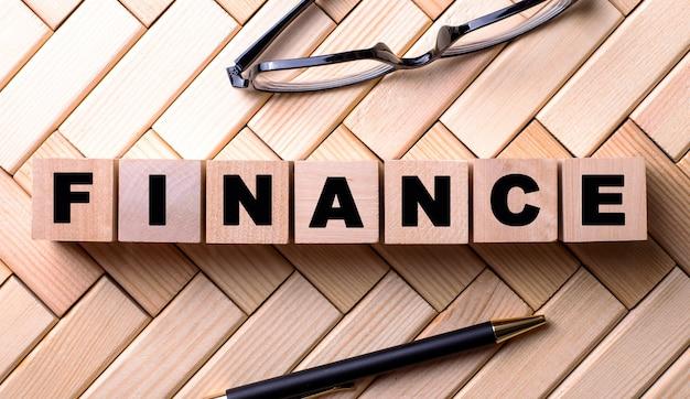 Слово финансы написано на деревянных кубиках на деревянном фоне рядом с ручкой и очками.