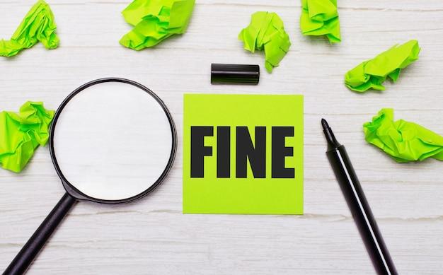 虫眼鏡の横にある緑色の付箋紙と木製のテーブルの黒いマーカーに書かれたfineという単語