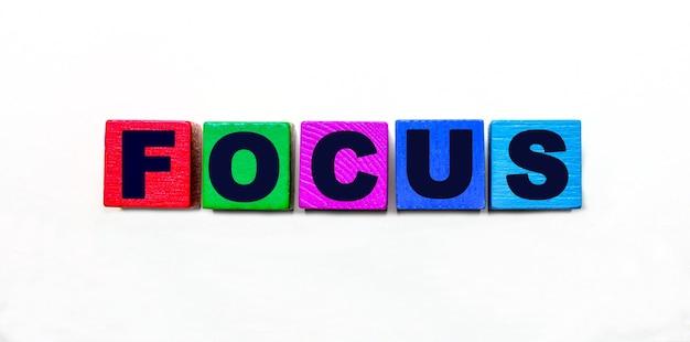 Слово focus написано на разноцветных кубиках на светлом фоне.