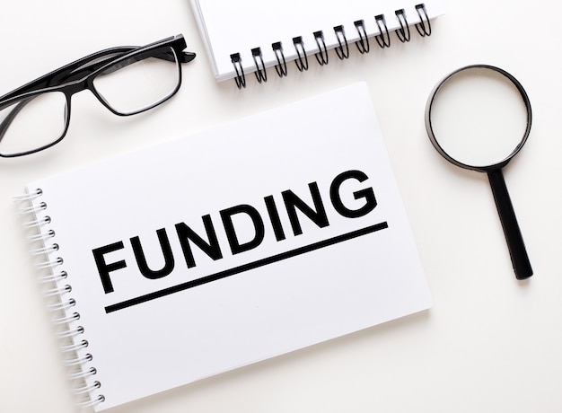 Слово финансирование написано в белом блокноте на светлом фоне рядом с блокнотом, очками в черной оправе и увеличительным стеклом.