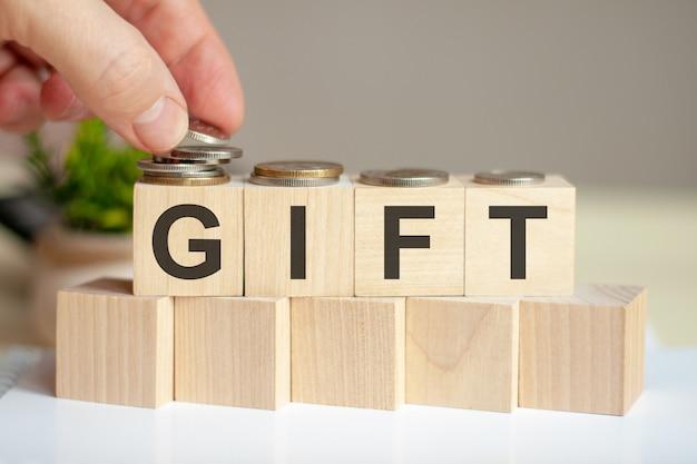 나무 조각에 쓰여진 단어 선물. 사람의 손이 입방체 표면에 동전을 놓습니다.