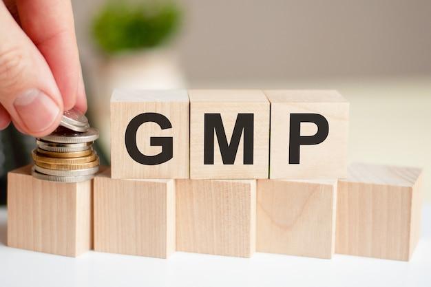 나무 큐브에 쓰여진 단어 gmp. 사람의 손이 입방체 표면에 동전을 놓습니다.