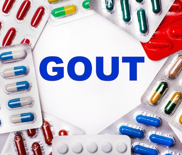 痛風という言葉は、錠剤が入った色とりどりのパッケージに囲まれたライトテーブルに書かれています。医療の概念