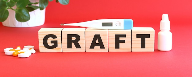 Слово graft состоит из деревянных кубиков на красном фоне с лекарствами.