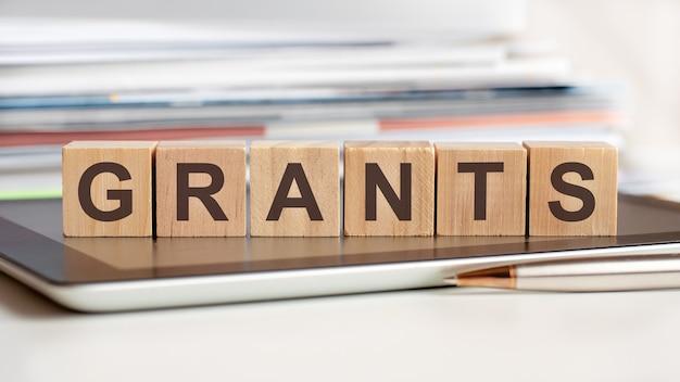 Слово гранты написано на деревянных кубиках, стоящих на блокноте, на поверхности стопка документов.