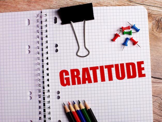 Gratitudeという言葉は、木製の壁にあるマルチカラーの鉛筆とボタンの近くのノートに書かれています。
