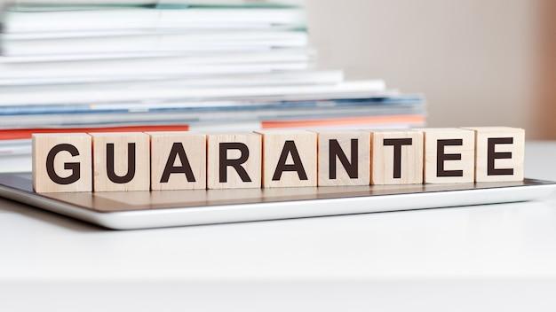 Слово «гарантия» написано на деревянных кубиках, стоящих на блокноте. может использоваться для бизнеса, образования, финансовой концепции.