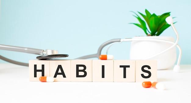 На деревянных кубиках написано слово привычки.