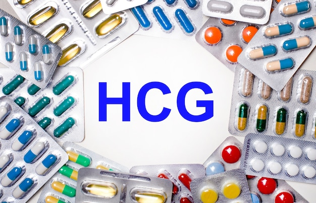 Hcgヒト絨毛性ゴナドトロピンという言葉は、錠剤が入ったマルチカラーのパッケージに囲まれた明るい背景に書かれています。医療コンセプト