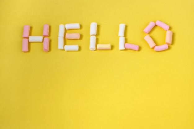 「こんにちは」という言葉は、黄色の背景にマルチカラーのマシュマロで配置されています。はがきまたはカードのモックアップ、クローズアップ上面図