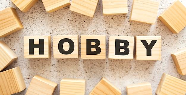 Слово hobby состоит из деревянных кубиков с буквами, вид сверху на светлой поверхности.