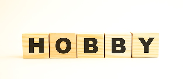 Слово хобби. деревянные кубики с буквами на белом фоне. концептуальный образ.